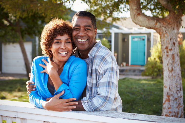 Brunette husband and wife embraces while smiling with their dental implants in front of the home with a blue door